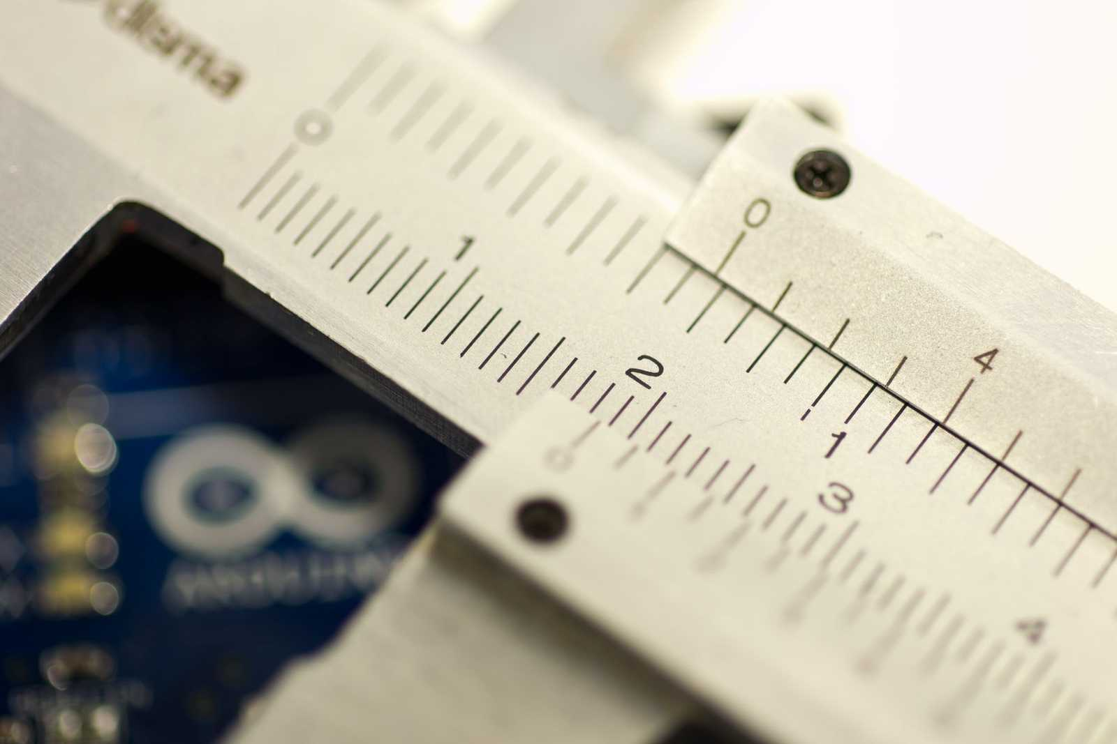 zoomed in view of silver analog calipers with a blue circuit board in background