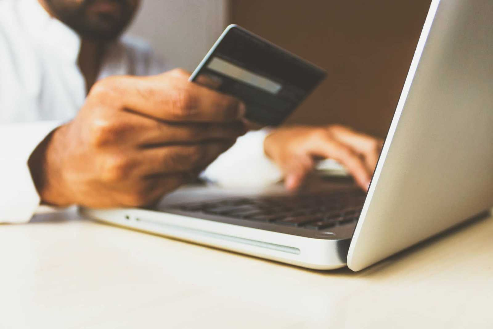 a closeup of a man's hand holding a credit card, presumably making an online purchase