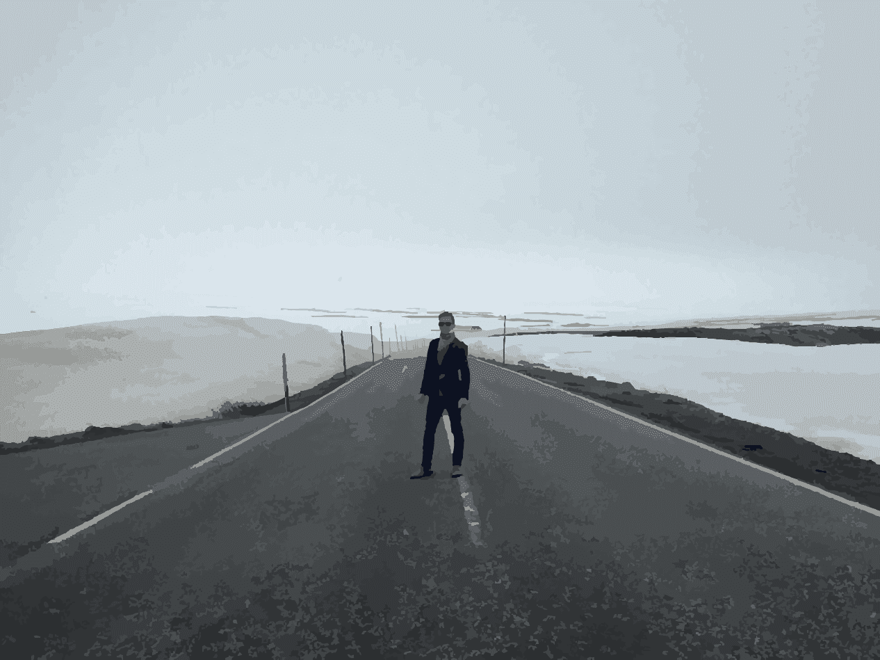 the author standing in the middle of a desolate road with snowbanks to either side