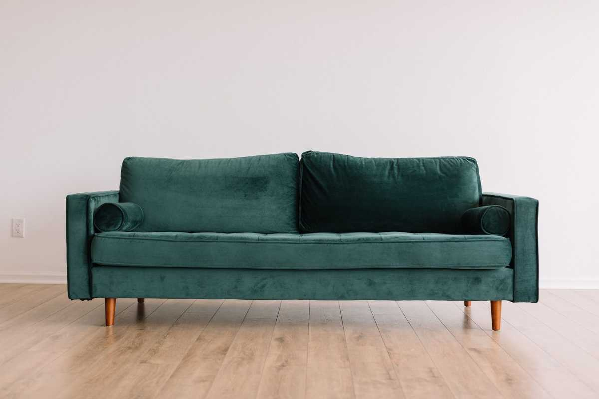 a green velvet sofa in an empty room with wooden floors